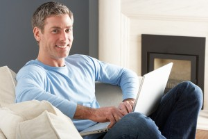 bigstock-Man-Using-Laptop-Relaxing-Sitt-27382526
